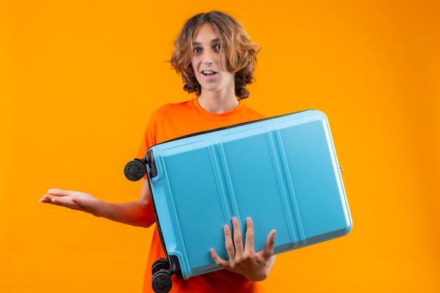 Młody przystojny facet w pomarańczowej koszulce trzymający walizkę podróżną nieświadomy i zdezorientowany, nie mając odpowiedzi, rozkładając ręce stojąc na żółtym tle
