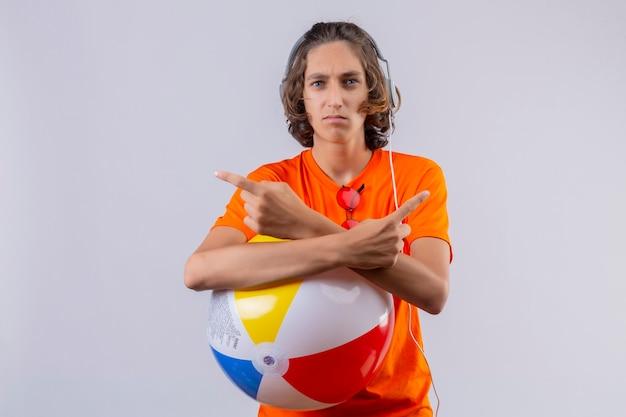 Młody przystojny facet w pomarańczowej koszulce ze słuchawkami trzymającymi nadmuchiwaną piłkę skrzyżowanymi rękami wskazującymi palcami na boki patrząc na kamerę z marszczoną twarzą stojącą na białym tle