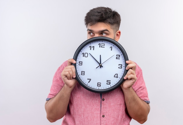 Młody przystojny facet w różowej koszulce polo chowający się poza zegarem i zastanawiający się, czy spóźnia się na białą ścianę