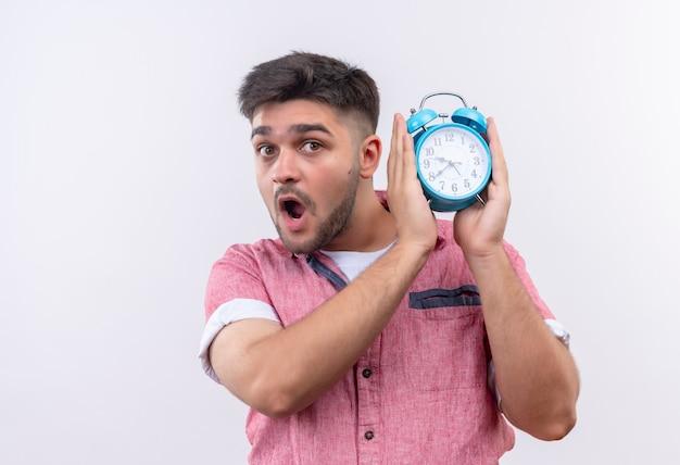 Młody przystojny facet w różowej koszulce polo z niebieskim budzikiem ostrzega przed spóźnieniem na białej ścianie