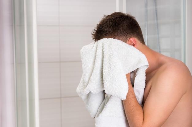 Młody przystojny facet wyciera twarz czystym ręcznikiem po zabiegach mycia w nowoczesnej, wyłożonej kafelkami łazience