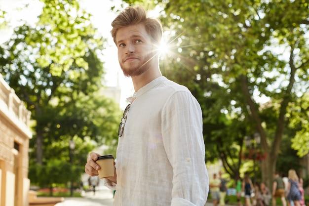 Młody przystojny facet z rudymi włosami i brodą w białej koszuli w parku