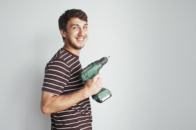 Młody przystojny facet ze śrubokrętem wierci białą ścianę w nowym mieszkaniu, robi naprawy.