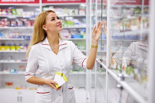 Młody przystojny farmaceuty kobieta szuka leków na półkach aptecznych