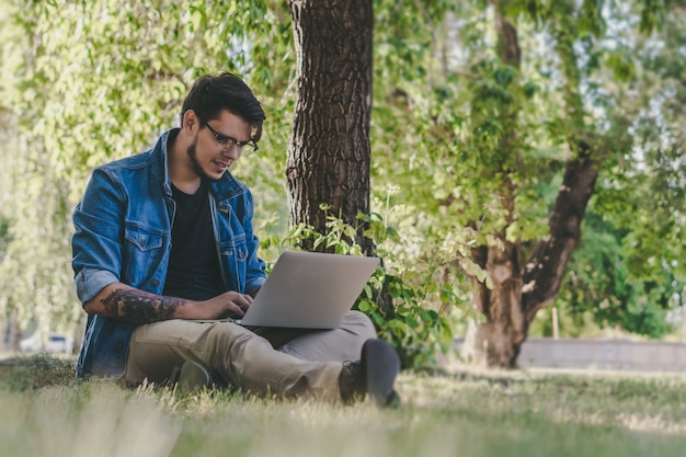 Młody przystojny freelancer pracuje na laptopie outdoors. koncepcja pracy na zewnątrz.