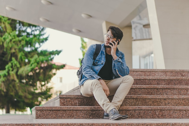 Młody przystojny freelancer rozmawia przez telefon na zewnątrz. koncepcja pracy na zewnątrz.