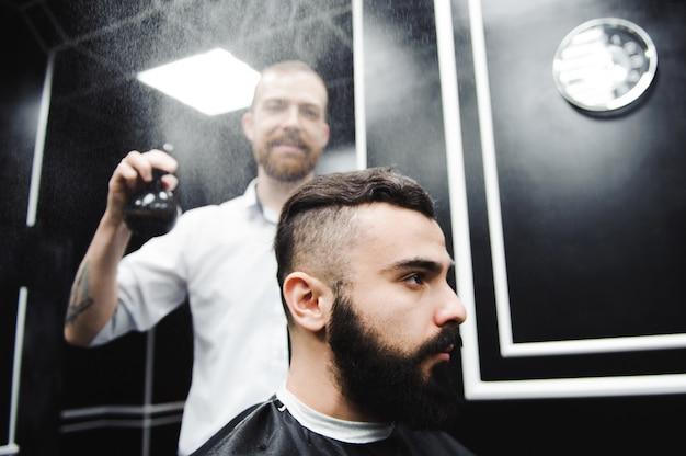 Młody przystojny fryzjer co fryzura atrakcyjnego mężczyzny