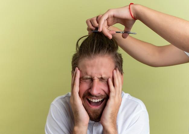 Młody przystojny fryzjer kładący dłonie na twarzy z zamkniętymi oczami, przestraszony tym, że wszystkie jego włosy zostaną obcięte na tle oliwkowej zieleni z miejscem na kopię