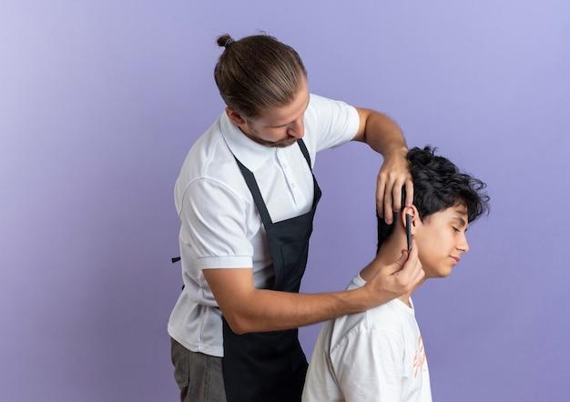 Młody przystojny fryzjer na sobie mundur stojący w widoku profilu robi fryzurę dla młodego klienta na białym tle na fioletowym tle z miejsca na kopię