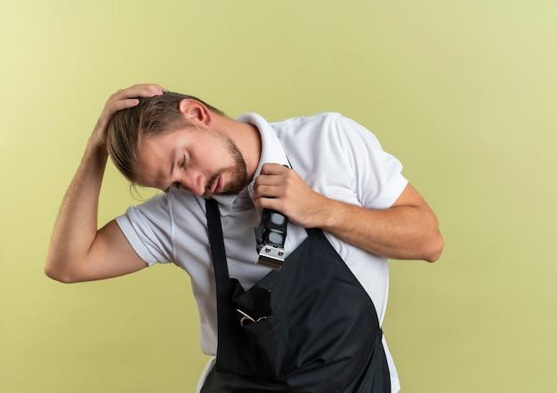 Młody przystojny fryzjer trzymając maszynkę do strzyżenia włosów kładąc rękę na głowie z zamkniętymi oczami na białym tle na oliwkowym tle
