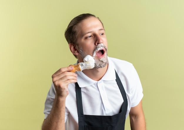 Młody przystojny fryzjer ubrany w mundur nakładający krem do golenia na brodę z pędzelkiem do golenia i patrząc na bok na białym tle na oliwkowym tle