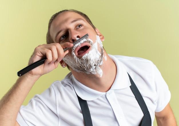Młody przystojny fryzjer w mundurze goli wąsy z prostą brzytwą patrząc w górę z kremem do golenia na twarzy odizolowany na oliwkowym tle