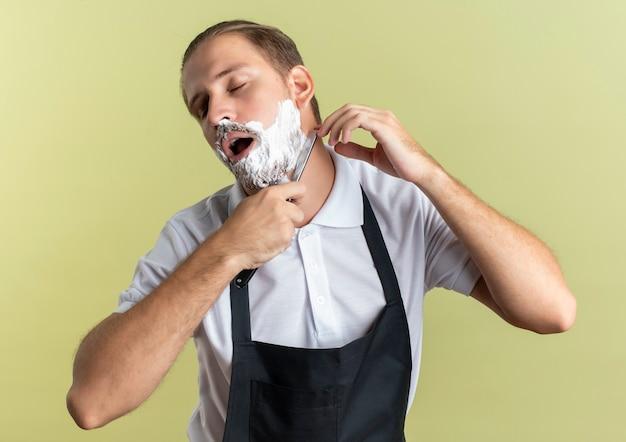 Młody przystojny fryzjer w mundurze, goli własną brodę z brzytwą z zamkniętymi oczami na białym tle na oliwkowym tle