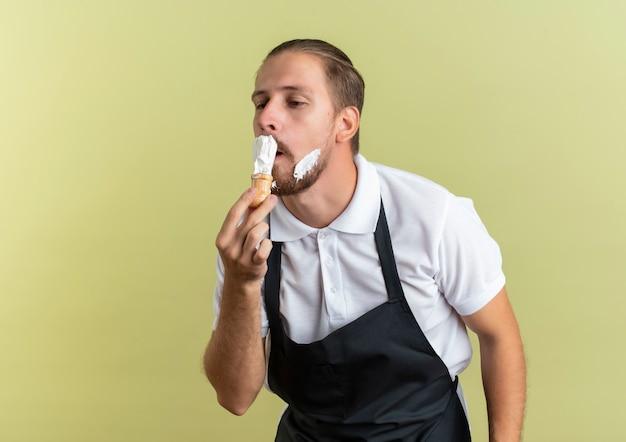 Młody przystojny fryzjer w mundurze trzymając pędzel do golenia nakładający krem do golenia na własną brodę patrząc na bok na białym tle na oliwkowym tle z miejsca na kopię