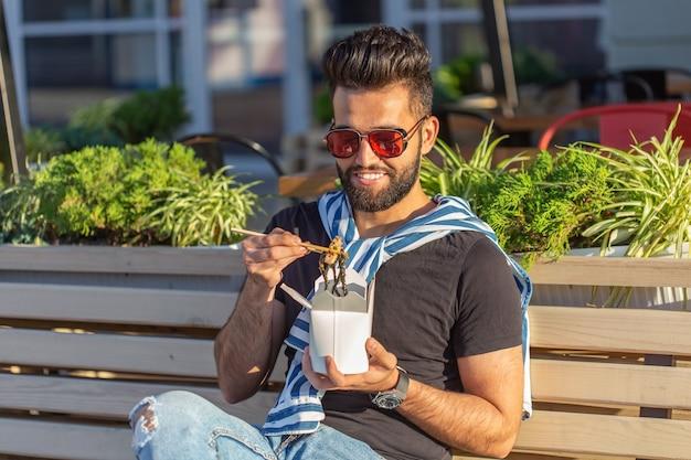 Młody przystojny hipster facet je chiński makaron z pudełka na lunch, siedząc na ławce w parku w słoneczny letni dzień. koncepcja zdrowej i pożywnej przekąski.