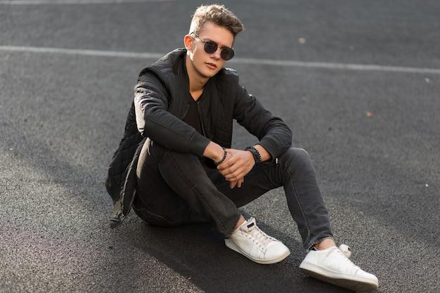 Młody przystojny hipster facet z okulary w modne czarne ubrania z kurtką i stylowe białe trampki siedząc na ulicy
