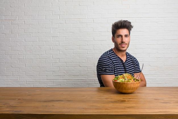 Młody przystojny i naturalny mężczyzna siedzi na stole krzyżując ramiona, uśmiechnięty i szczęśliwy, będąc pewny siebie i przyjazny. jedzenie świeżej sałatki.