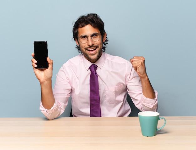 Młody przystojny indianin czuje się zszokowany, podekscytowany i szczęśliwy, śmiejąc się i świętując sukces, mówiąc wow!. pomysł na biznes