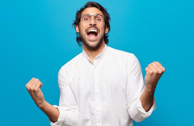 Młody przystojny indianin świętuje triumfalną ekspresję