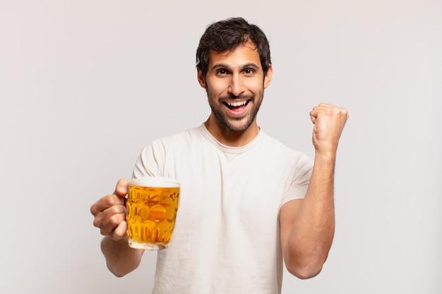 Młody przystojny indianin świętuje zwycięstwo i trzyma piwo