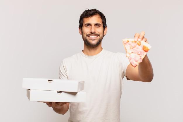 Młody przystojny indianin szczęśliwy wyraz twarzy i trzymający na wynos pizze