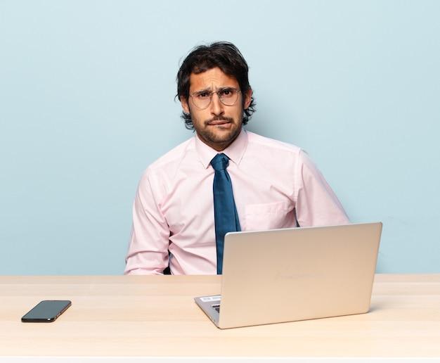 Młody przystojny indianin wyglądający na zdziwionego i zdezorientowanego, przygryzający wargę nerwowym gestem, nie znający odpowiedzi na problem. koncepcja biznesu i frelancer