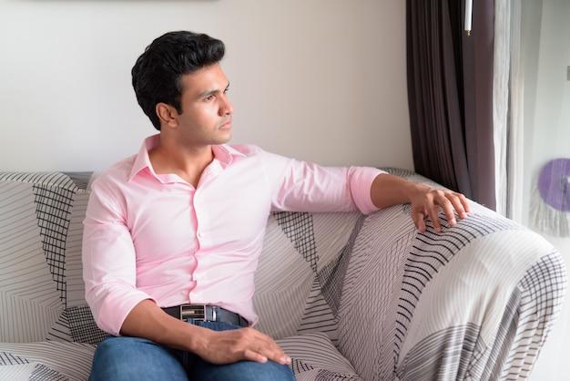 Młody przystojny indyjski biznesmen myśli i patrząc przez okno w salonie w domu