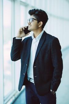 Młody przystojny indyjski biznesmen opowiada na telefonie komórkowym w nowożytnym biurze