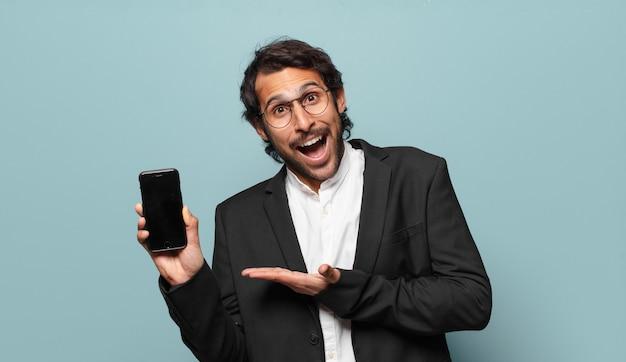 Młody przystojny indyjski biznesmen pokazujący pusty ekran telefonu