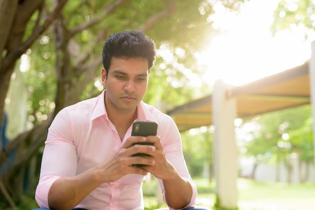 Młody przystojny indyjski biznesmen przy użyciu telefonu w parku