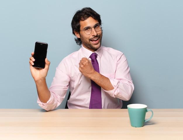 Młody przystojny indyjski mężczyzna czuje się szczęśliwy, pozytywny i odnoszący sukcesy, zmotywowany, gdy staje przed wyzwaniem lub świętuje dobre wyniki. pomysł na biznes