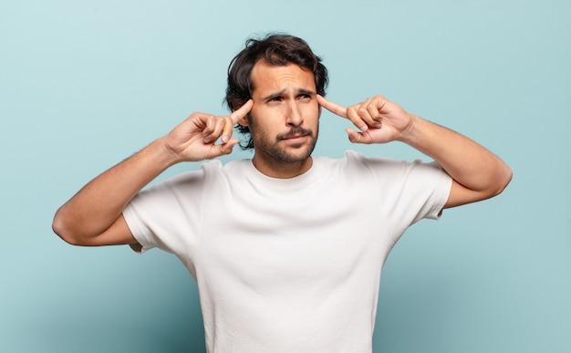Młody przystojny indyjski mężczyzna czuje się zdezorientowany lub wątpi, koncentruje się na pomyśle, intensywnie myśli, chce skopiować miejsce z boku