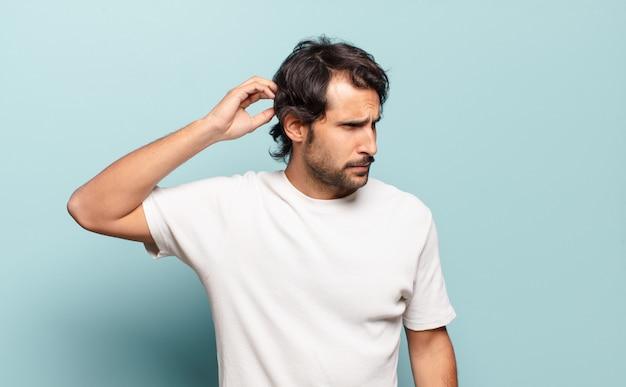 Młody przystojny indyjski mężczyzna czuje się zdziwiony i zdezorientowany, drapiąc się po głowie i patrząc w bok
