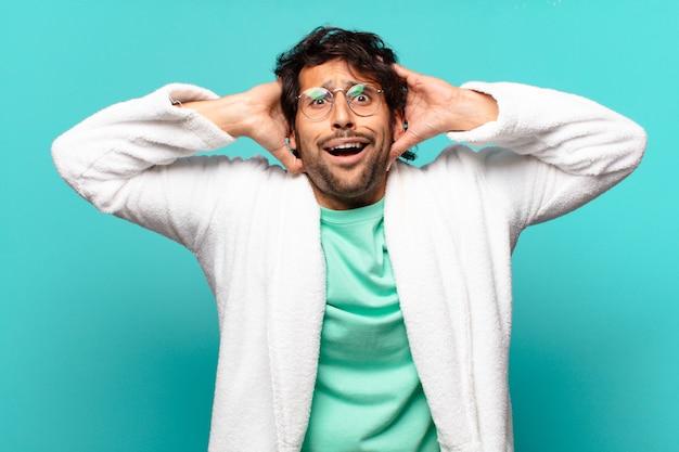 Młody przystojny indyjski mężczyzna czuje się zestresowany, zmartwiony, niespokojny lub przestraszony, z rękami na głowie, panikuje podczas pomyłki i nosi szlafrok