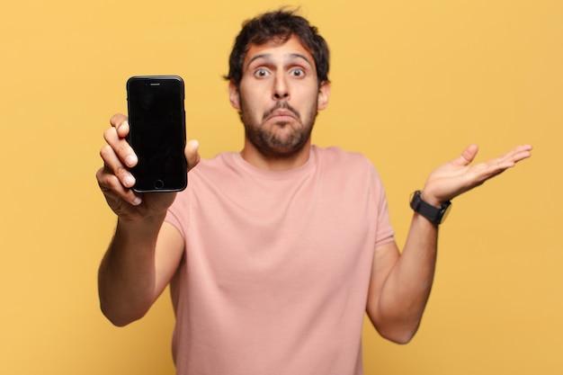 Młody przystojny indyjski mężczyzna mylić koncepcję smartfona wyrażenie
