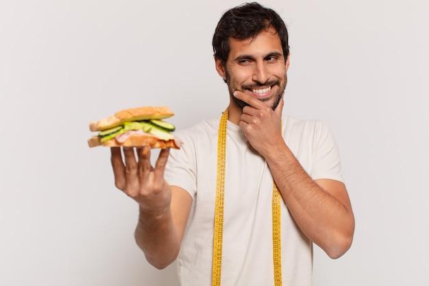 Młody przystojny indyjski mężczyzna myśli wyrażenie i trzyma kanapkę