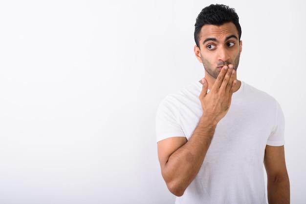 Młody przystojny indyjski mężczyzna przeciw białemu tłu