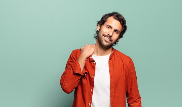 Młody przystojny indyjski mężczyzna śmiejący się wesoło i pewnie z przypadkowym, szczęśliwym, przyjaznym uśmiechem