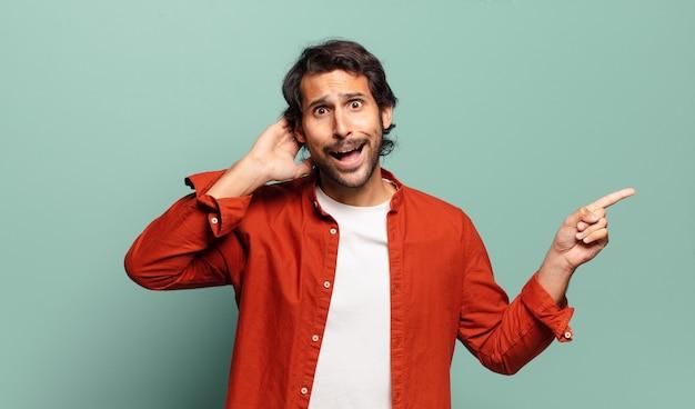 Młody przystojny indyjski mężczyzna śmieje się, wygląda na szczęśliwego, pozytywnego i zdziwionego, realizując świetny pomysł wskazujący na boczną przestrzeń kopii