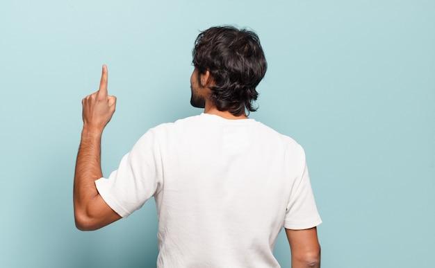 Młody przystojny indyjski mężczyzna stojący i wskazujący na obiekt na przestrzeni kopii, widok z tyłu
