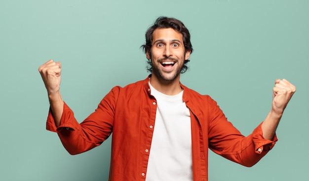 Młody przystojny indyjski mężczyzna świętujący niewiarygodny sukces jak zwycięzca, wyglądający na podekscytowanego i szczęśliwego, mówiąc: weź to!