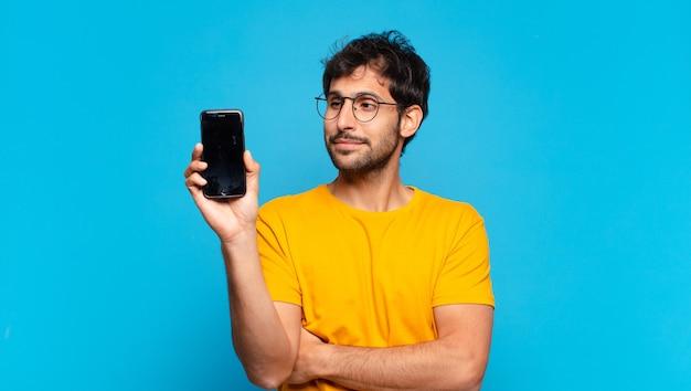 Młody przystojny indyjski mężczyzna szczęśliwe wyrażenie i trzymający telefon komórkowy