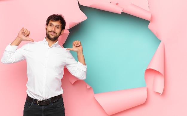 Młody przystojny indyjski mężczyzna szczęśliwy wyraz na tle złamanego papieru dziury