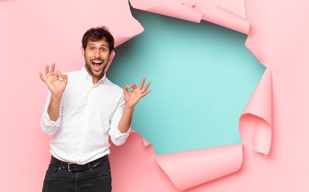 Młody przystojny indyjski mężczyzna szczęśliwy wyraz na tle złamanej dziury papieru