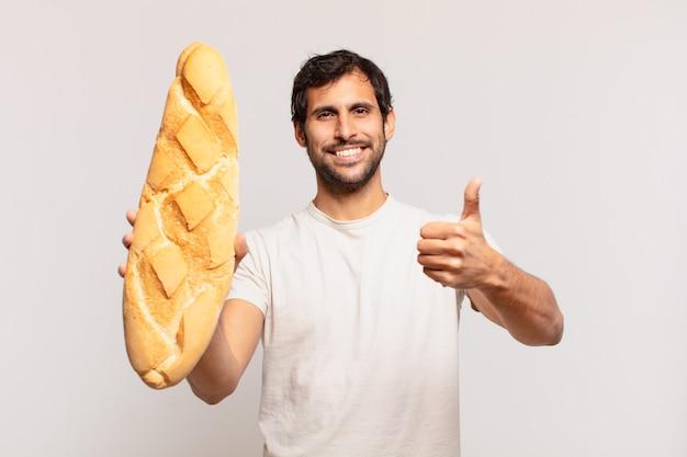 Młody przystojny indyjski mężczyzna szczęśliwy wyraz twarzy i trzymający chleb
