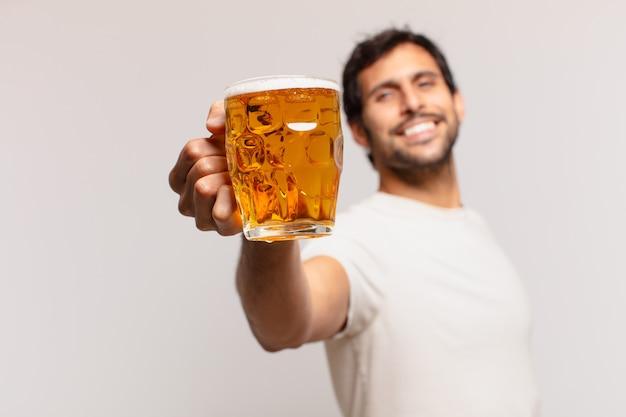 Młody przystojny indyjski mężczyzna szczęśliwy wyraz twarzy i trzymający piwo