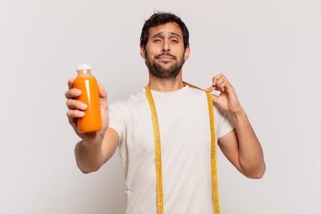 Młody przystojny indyjski mężczyzna szczęśliwy wyraz twarzy i trzymający smoothy
