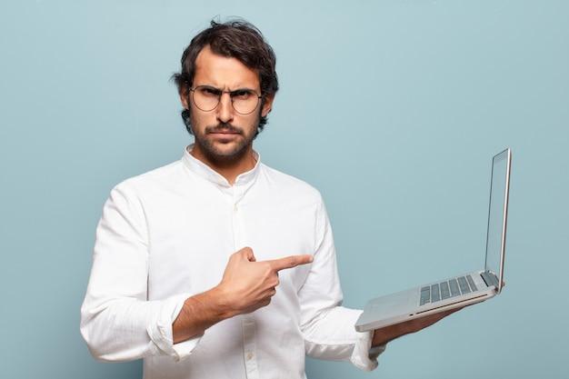 Młody przystojny indyjski mężczyzna trzyma laptopa. koncepcja biznesu lub mediów społecznościowych