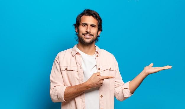 Młody przystojny indyjski mężczyzna uśmiecha się, czuje się szczęśliwy, beztroski i zadowolony, wskazując na koncepcję lub pomysł na kopiowanie miejsca z boku