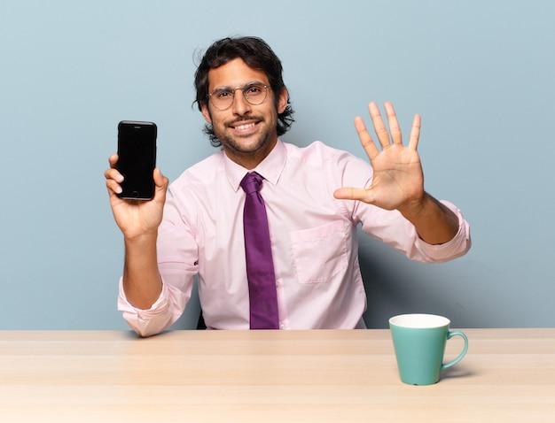 Młody przystojny indyjski mężczyzna uśmiecha się i wygląda przyjaźnie, pokazując numer pięć lub piąty z ręką do przodu, odliczając